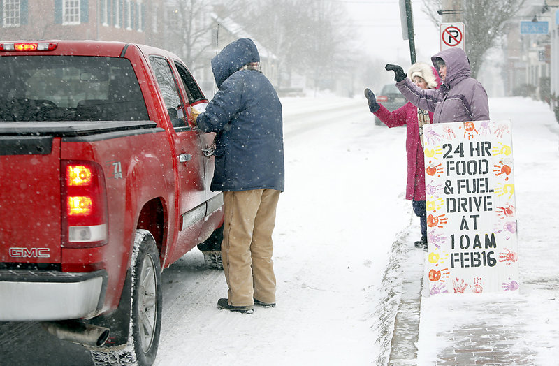Sue Mack collects a donation from a passenger, as Patti Bruce, center, and Paula O'Brien wave Sunday in front of the First Parish Church on Main Street in Freeport.