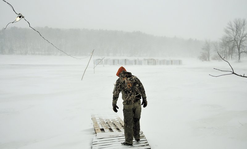 Jordan Mayo heads out to clean camps at Sonny's Smelt Fishing on the frozen Kennebec River in Dresden on Sunday. Winds gusted to 30 mph and blowing snow limited visibility to less than 100 yards.