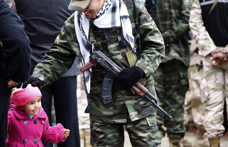"A member of the Libyan security forces pats a child while celebrating the revolution's anniversary in Benghazi, on Sunday. In their new society, Libyans are impatient for ""transitional justice."""