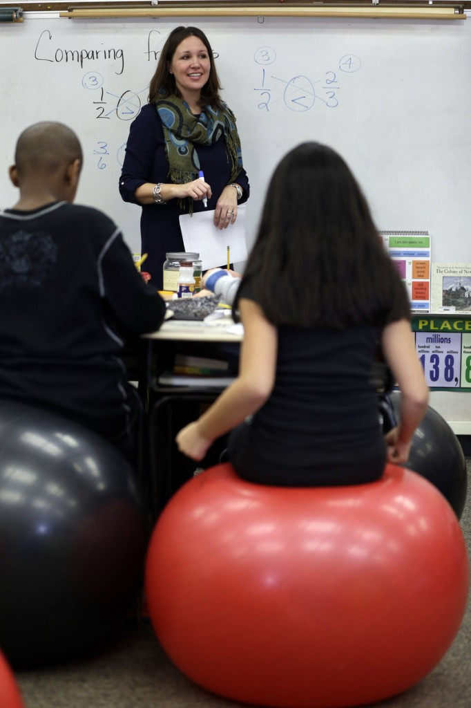 Robbi Giuliano teaches her fifth graders as they use their muscles to balance on yoga balls, a practice that increases blood flow, leading to more alertness.