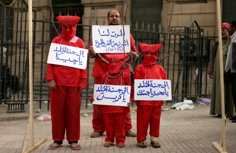 An Egyptian man and his three children wear red during a symbolic hanging at an anti-government protest in front of Egypt's high court building in downtown Cairo on Friday.