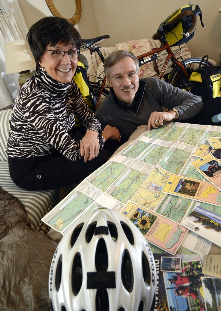 Debbie and Tim Bishop, at their home in Marlborough, Mass., show some of the maps they used on their honeymoon bicycle trip from Seaside, Ore., to Cape Elizabeth, Maine.