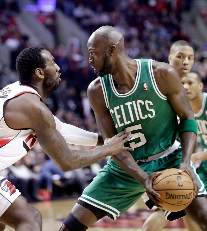 Boston forward Kevin Garnett looks for an opening against Portland center J.J. Hickson during first-quarter action of Sunday's game, won by the Trail Blazers.