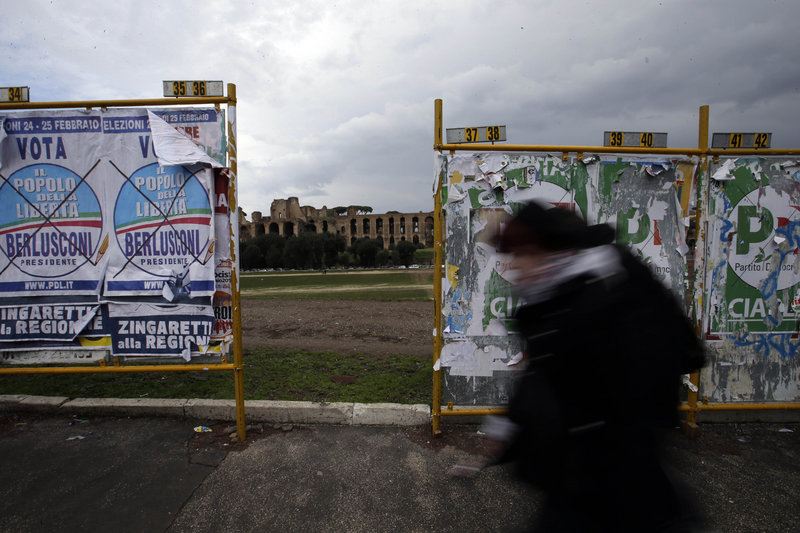 A man walks past election posters in Rome, with the Palatine hill in the background, on Monday. Italy's crucial elections appear to be heading toward gridlock, initial results show.