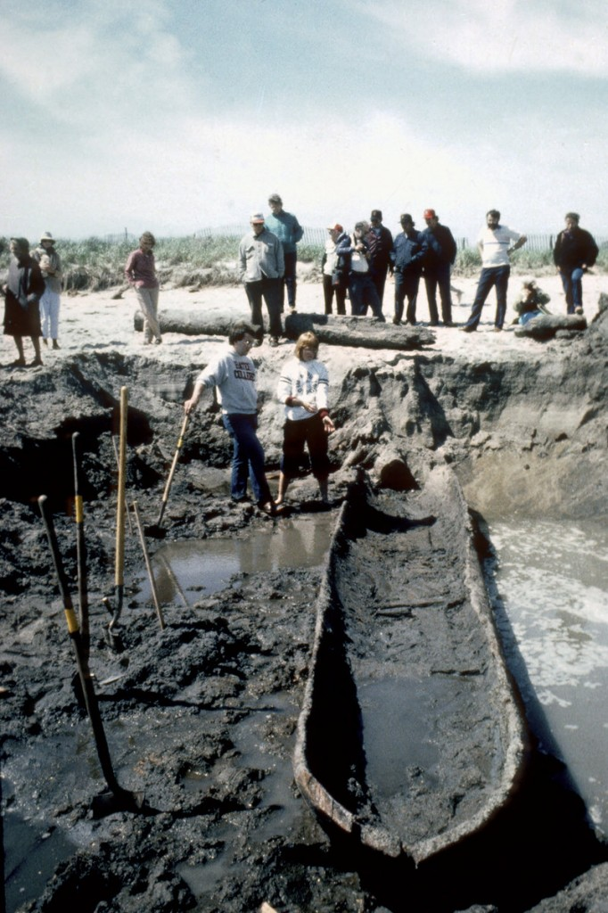 Volunteers Kirk Upton, front left, and Christine Styrna stand near a dugout canoe as it is excavated from a beach in Biddeford Pool on June 4, 1986. The canoe, believed to be from the eighteenth-century and made by early settlers, has been stored in Massachusetts for the past 25 years.