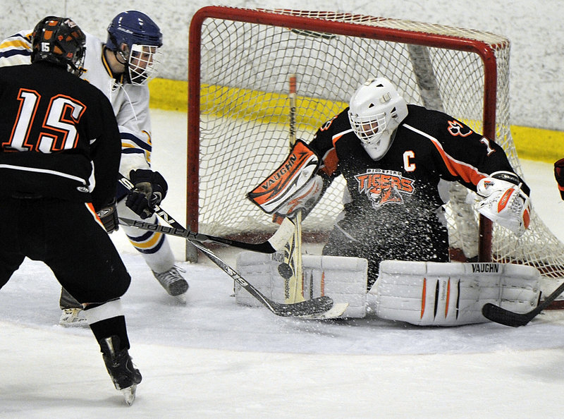Biddeford goalie Jon Fields keeps his focus and denies Billy Mullin of Falmouth on a rebound as Wyatt Leblond helps to defend. Falmouth improved to 15-3-1 and outshot the Tigers, 46-14.