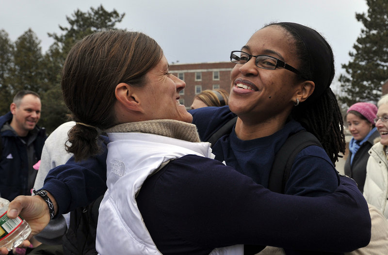 UMaine assistant coach Jhasmin Player, right, receives a hug from former director of basketball operations Tracey Guerette, as the women's basketball team returned to Orono on Wednesday evening, Feb. 27, 2013, after being involved in a harrowing crash on I-95 in Massachusetts on Tuesday night.