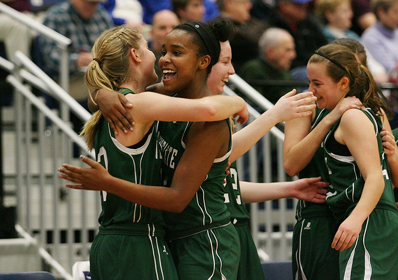 Rhiannan Jackson, center, hugs Martha Veroneau after Waynflete captured the Western Class C title by defeating Madison 63-41 at the Augusta Civic Center.