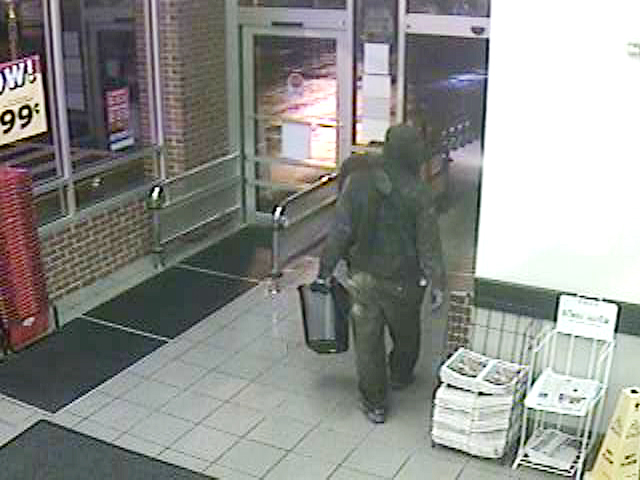 Surveillance photo of suspect leaving the Hannaford store carrying a plastic trashcan.