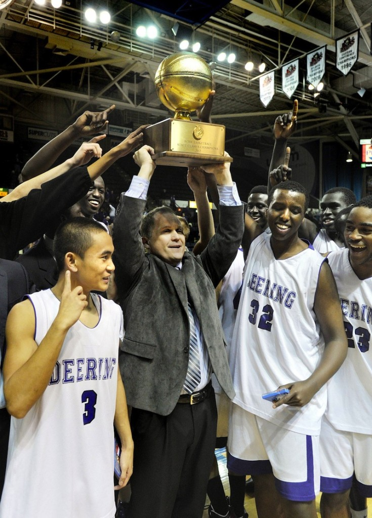 In this March 2012 file photo, Deering head coach Dan LeGage holds the state championship trophy along with his players following their win over Hampden Academy.
