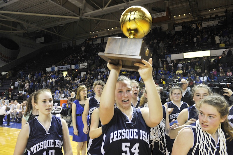Presque Isle's Meredith Stewart, No. 54, carries the Class B state championship trophy following her teams win over the Lakers. It is Presque Isle's second straight title.