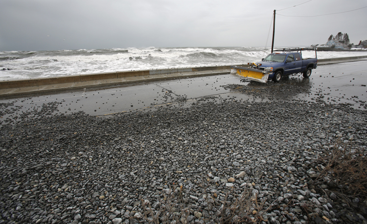 Stones tossed over a seawall by large waves cover Beach Avenue in Kennebunk on Friday.