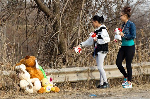 Dominique Ellison, left, and Rickie Bowling, of Warren, bring stuffed animals to a memorial in honor of their friends who died in a car crash on Park Ave. in Warren, Ohio on Sunday, March 10, 2013. (AP Photo/Scott R. Galvin)