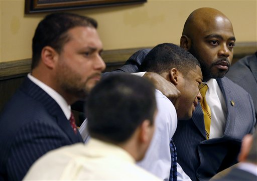 Defense attorney Walter Madison, right, holds his client, 16-year-old Ma'Lik Richmond, second from right, while defense attorney Adam Nemann, left, sits with his client Trent Mays, foreground, 17, in Steubenville, Ohio, on Sunday, as Juvenile Court Judge Thomas Lipps pronounces them both guilty of raping a drunken classmate.