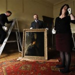 Buckland Abbey staff prepare to hang a recently confirmed self-portrait of Rembrandt.