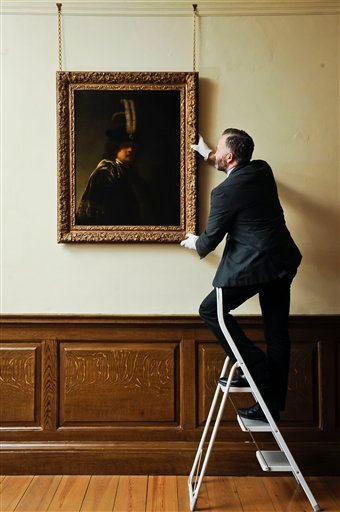 David Taylor, curator of pictures and sculpture at Buckland Abbey, adjusts the newly confirmed self-portrait by Rembrandt discovered at Devonshire Abbey, in Skipton, England. The masterpiece was gifted in 2010 to Britain's National Trust by the family estate of a wealthy property developer, and has now undergone detailed investigations led by the world's leading Rembrandt expert, Ernst van de Wetering, to determine its provenance before declaring it an original painting by the Dutch master.