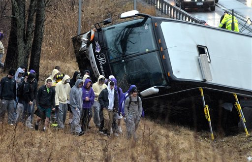 Members of the St. Michael's College lacrosse team walk away from the wrecked bus that was carrying them after it crashed on Tuesday.
