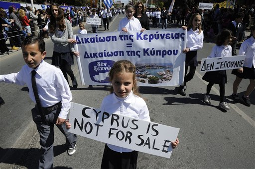 "Students hold placards during a parade for Greek independence day celebrations at the southern port city of Limassol, Cyprus on Monday. Cyprus secured what its politicians described as a ""painful"" solution to avert imminent bankruptcy, agreeing early Monday to slash its oversize banking sector and make large account holders take losses to help pay to secure a last-minute euro10 billion (US$13 billion) bailout."