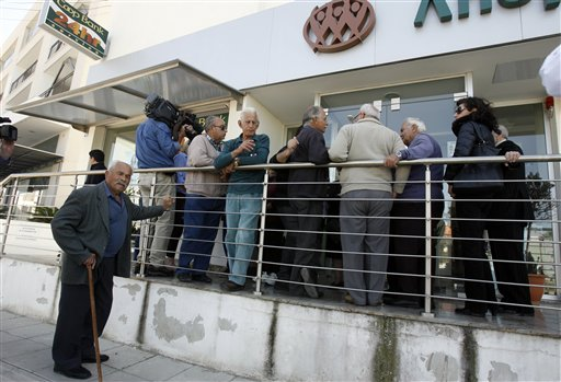 People wait outside a Coop bank branch in Nicosia, Cyprus, on Thursday. Bank branches across the country were being replenished with cash, and were scheduled to open for six hours at noon.