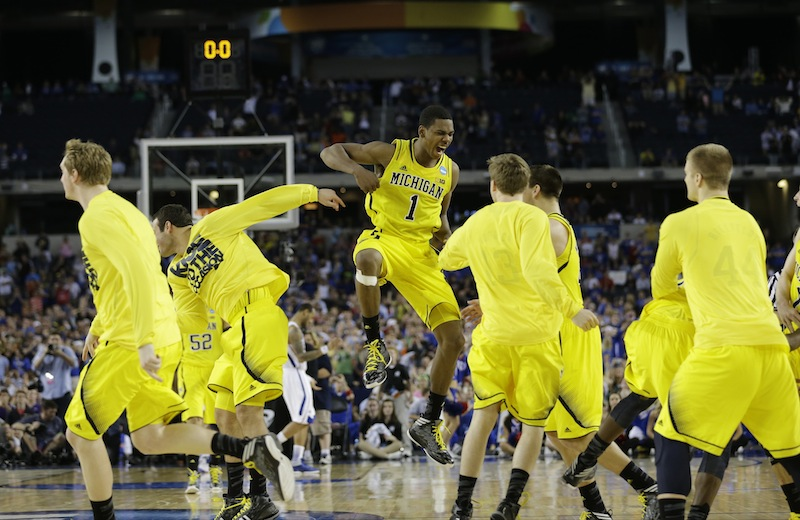 Michigan's Glenn Robinson III (1) and teammates celebrate after beating Kansas 87-85 in overtime of a regional semifinal game in the NCAA college basketball tournament, Friday, March 29, 2013, in Arlington, Texas. (AP Photo/David J. Phillip)
