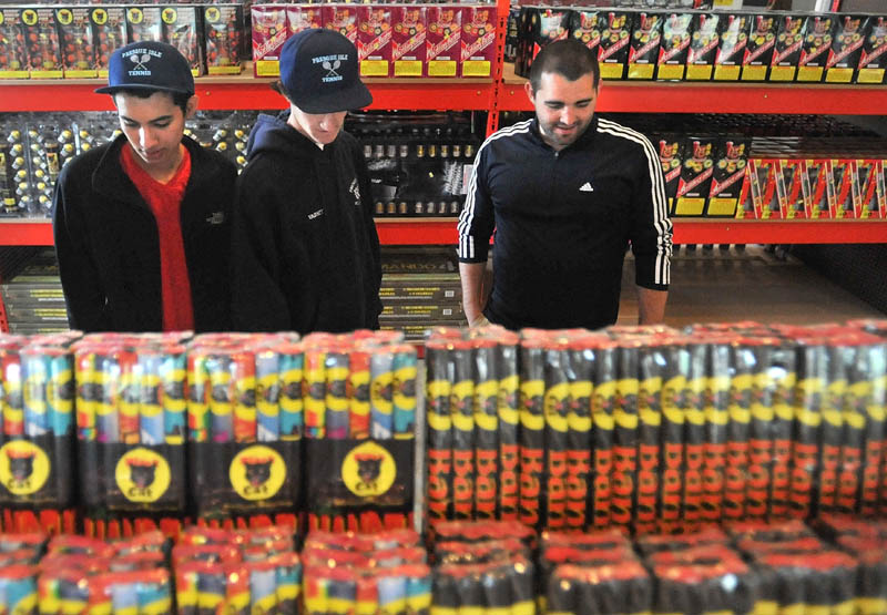 FIRED UP: Osman Castro, 18, left, Connor Shaw, 17, center, and Sam Picard, all from Presque Isle, browse the vast selection of fireworks at Pyro City Maine on China Road in Winslow Friday.