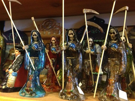 Statues of La Santa Muerte are shown at the Masks y Mas art store in Albuquerque, N.M., recently. In addition to showing up at drug crime scenes, the once-underground icon has been spotted on passion candles in Richmond, Va. grocery stores. The folk saint's image can be seen inside New York City apartments, in Minneapolis religious shops and during art shows in Tucson, Ariz.