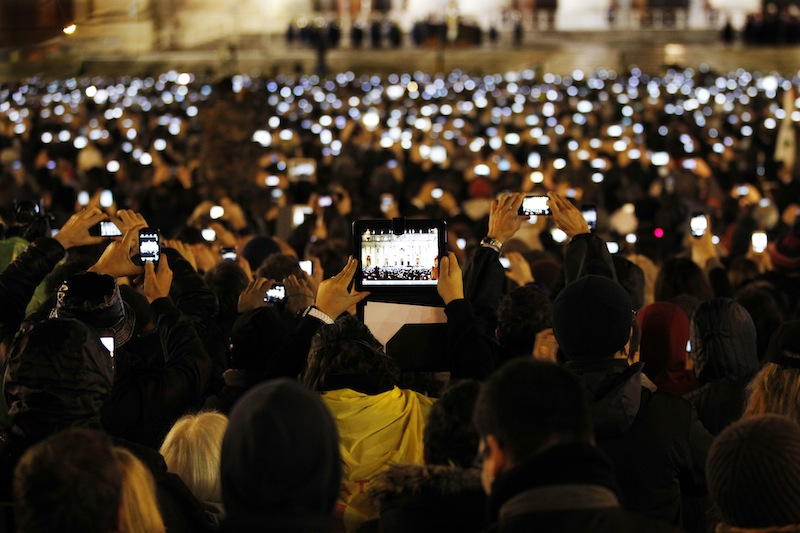 Visitors take photos of Pope Francis as he speaks from the central balcony of St. Peter's Basilica at the Vatican, Wednesday, March 13, 2013. Cardinal Jorge Bergoglio, who chose the name of Francis is the 266th pontiff of the Roman Catholic Church. (AP Photo/Michael Sohn)