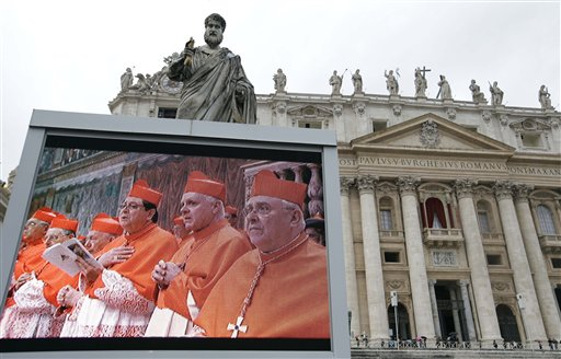 A giant monitor in St. Peter's Square at the Vatican, shows cardinals praying on Tuesday. Cardinals have begun the conclave to elect the next pope amid deep divisions and uncertainty over who will lead the 1.2 billion-strong Catholic church and tend to its many problems.
