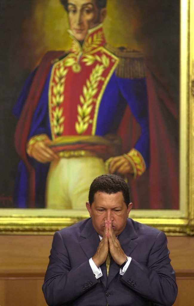 In this Dec. 5, 2001 file photo, Venezuela's President Hugo Chavez gestures before a painting of Venezuelan independence hero Simon Bolivar at an event at Miraflores presidential palace in Caracas, Venezuela. Venezuela's Vice President Nicolas Maduro announced on Tuesday, March 5, 2013 that Chavez has died. Chavez, 58, was first diagnosed with cancer in June 2011. (AP Photo/Leslie Mazoch, File)