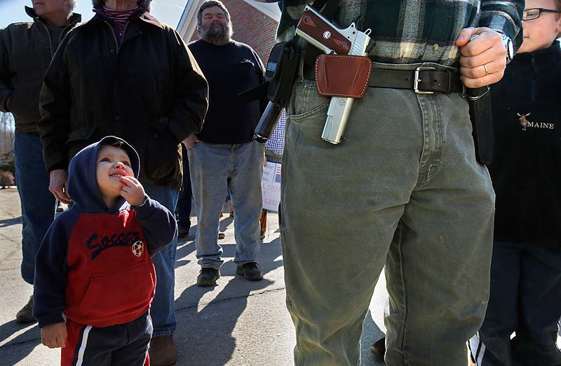Samson Hiltz, 2, looks up to his father, Jeremy Hiltz of Chelsea, pastor at the Windsor Memorial Baptist Church, while the two attend a rally protesting gun control legislation and supporting gun rights in Wiscasset on Saturday.