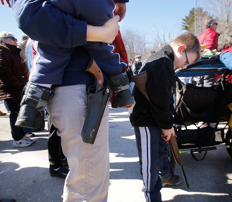 Suzanne Hiltz of Chelsea holds her son, Samson, 2, with a Ruger Single-Six .22 caliber revolver on her hip, while attending a rally in Wiscasset on Saturday protesting gun control legislation and supporting gun rights. At right is Hiltz's son Jonah, 7, holding a .22-caliber youth model rifle.