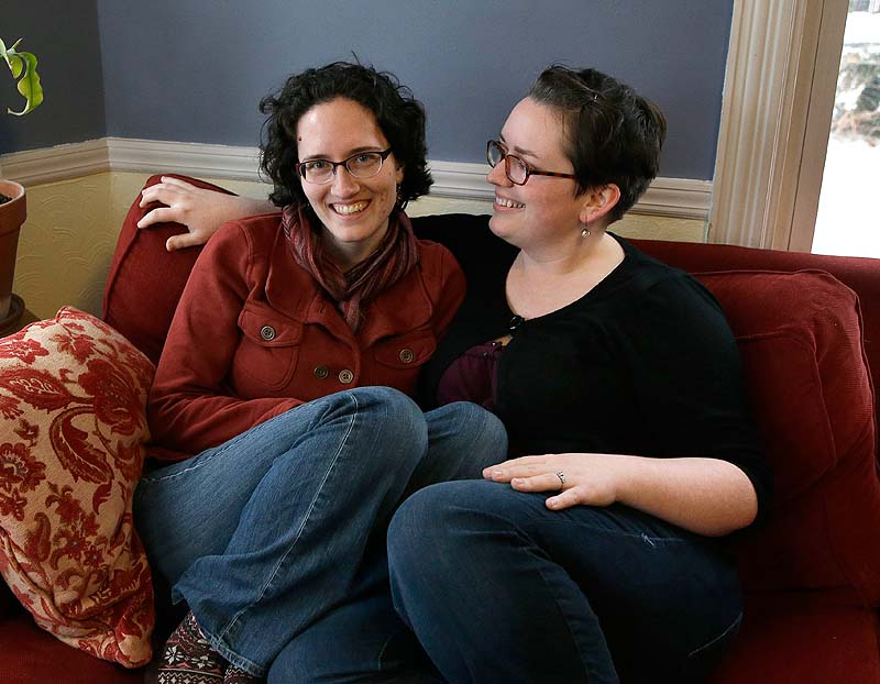 Amanda Hollander, left, and Katy McCormack sit together at their home in Portland last week. The women are getting married over Memorial Day weekend. They wanted to wait so they could invite friends and relatives and make all the arrangements that come with a wedding in which 224 people are being invited.