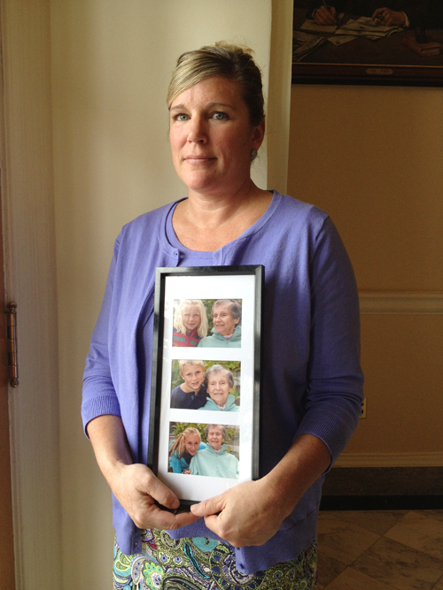 Sally Tartre of Kennebunk, whose late mother, Connie Roux, had Alzheimer's disease, spoke Thursday at a State House news conference presenting Maine's first strategic plan to address dementia-related issues. She holds a frame of photos of her three children taken with their grandmother six weeks before she died in December 2011.