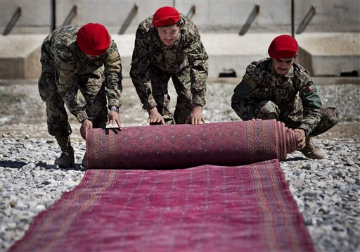 Afghan National Army soldiers roll up the red carpet after the hand over ceremony of the Parwan Detention Facility from U.S. military control to Afghan authorities in Bagram, outside Kabul, Afghanistan, Monday, March 25, 2013. The handover of Parwan Detention Facility ends a bitter chapter in American relations with Afghanistan's mercurial president, Hamid Karzai, who demanded control of the prison as a matter of national sovereignty. (AP Photo/Anja Niedringhaus)