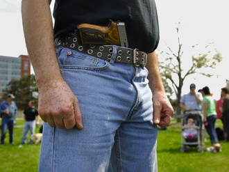In this April 2010 file photo, a pro-gun demonstrator who did not want to be identified stands in a park at Back Cove in Portland during a gathering to publicize the right to carry unconcealed weapons. The concealed-weapons permit data bill that sparked the year's most visceral public policy debate is up for its public hearing Tuesday, and a big crowd is expected.