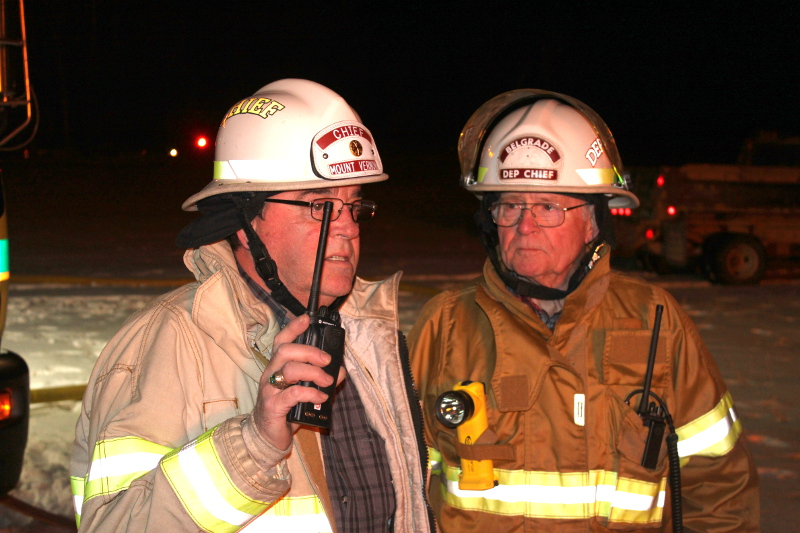 Mount Vernon Fire Chief Dana Dunn, left, and Belgrade Deputy Fire Chief Bill Pulsifer discuss tactics while fighting a fire on Bean Road in Mount Vernon on Sunday.
