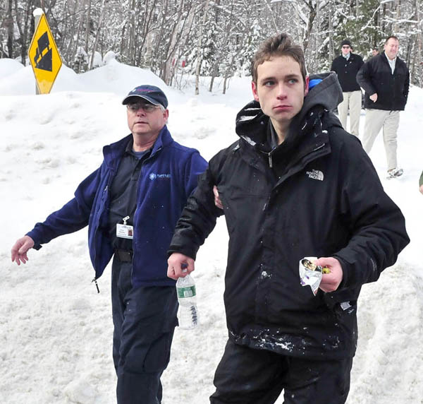 Staff photo by David Leaming Missing skier Nicholas Joy, 17, of Medford, Mass., is led to an ambulance Tuesday morning after spending two nights lost near Sugaloaf ski area.