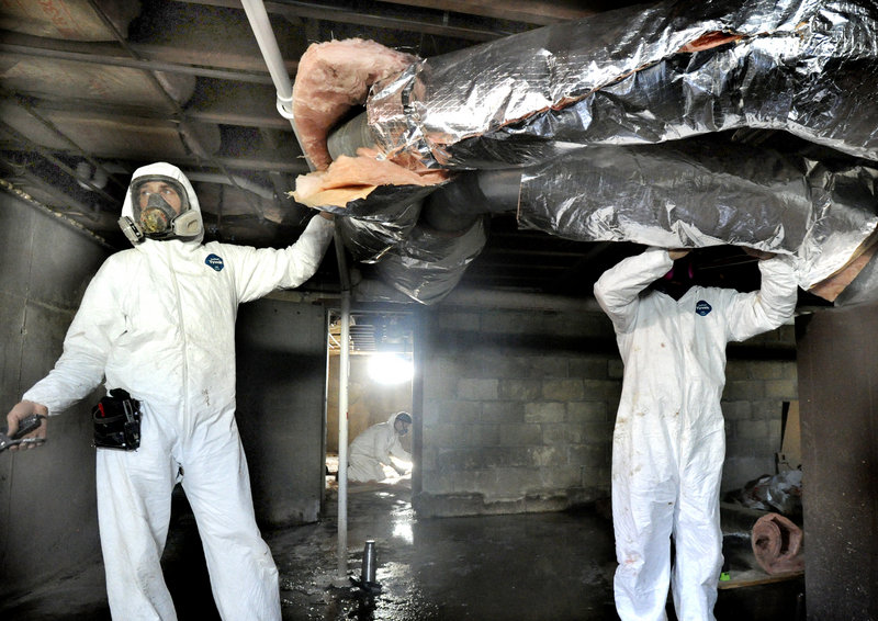 Michael Bunker, left, and Eddie Elwell of Evergreen Home Performance wrap insulation around heating ducts while weatherizing South Portland apartments. The most cost-effective way to spend $600 in most Maine homes is on weatherization and air-sealing.