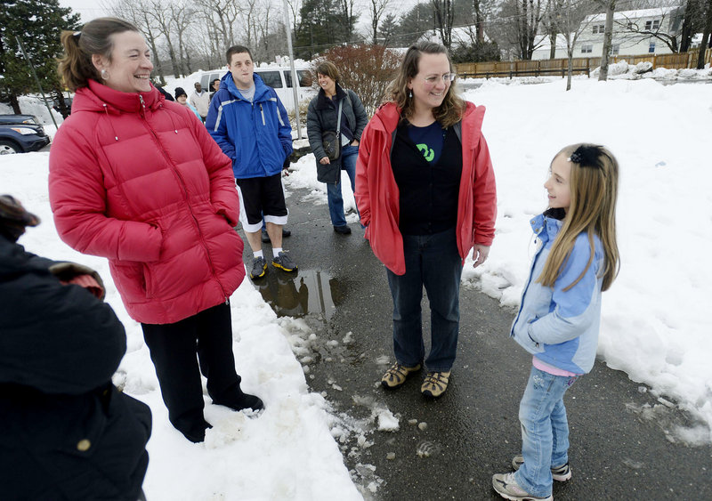"Cheryl Denis, center, greets her daughter Ella, 9, at Lyseth Elementary School on Thursday. ""I think it's great. It's really important for kids, not only for the health reasons, but it's just a great way to start the day,"" Denis said of the planned walking program. At left is Kelly Frost."