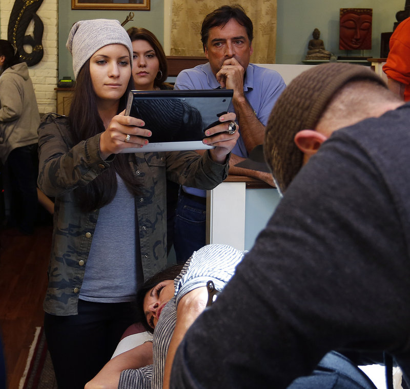 Kristian Spataro of Toronto takes a photo with a tablet device of her aunt, Sharon Boucher of Acton, Mass., getting a tattoo in honor of the late Robyn Hesseltine at Tsunami Tattoo in Portland on Thursday, Feb. 28, 2013.