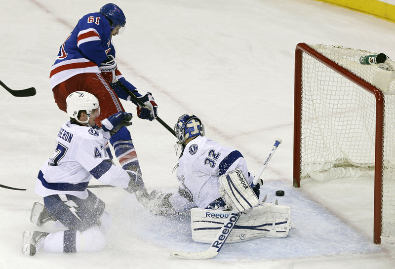 New York's Rick Nash slips the puck behind Tampa Bay goaltender Mathieu Garon during third-period action of Thursday's game, won by the Rangers.