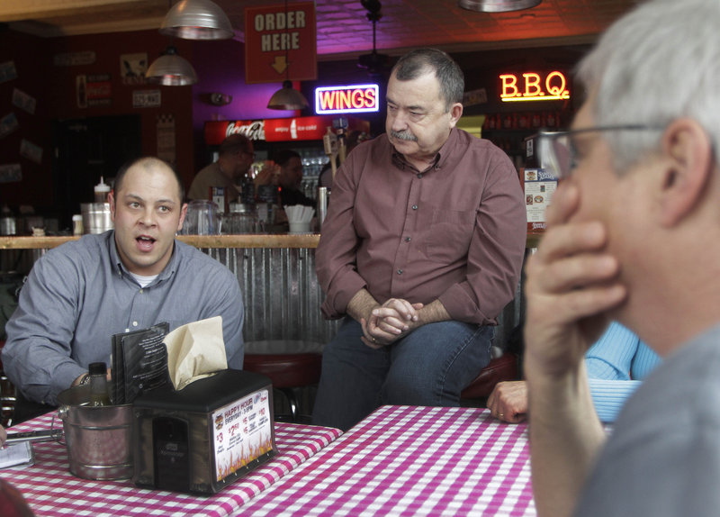 Portsmouth Naval Shipyard workers Kevin Do, left, Don Hanson and Paul O'Connor sit at nearby Mojo's BBQ in Kittery on Wednesday. They and other defense workers are bracing for reduced pay and possible layoffs due to federal budget cuts enacted Friday.