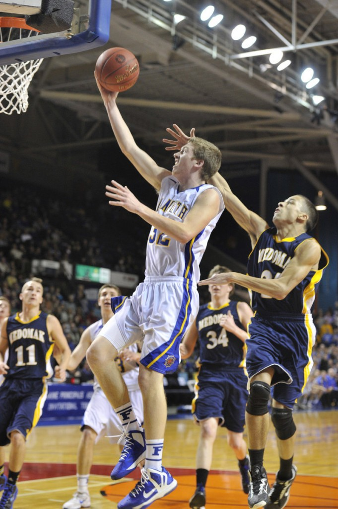 Justin Rogers of Falmouth drives the baseline past Jonathan Hendrickson-Belloguet of Medomak Valley during the 62-39 victory in the Class B final Friday.