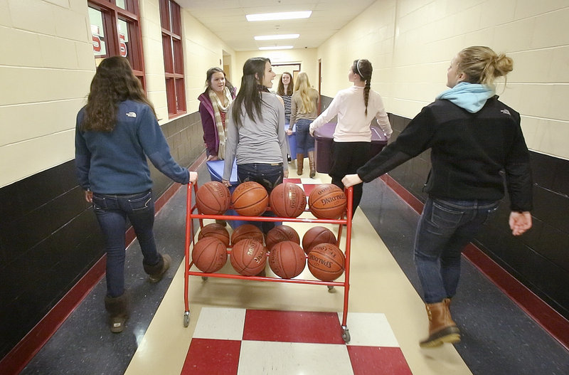 "Members of the Scarborough team bring gear to a storage room at the school after handing in their uniforms Feb. 27, the date of their last team meeting. ""We had a tremendous year,"" Coach Ron Cote said."
