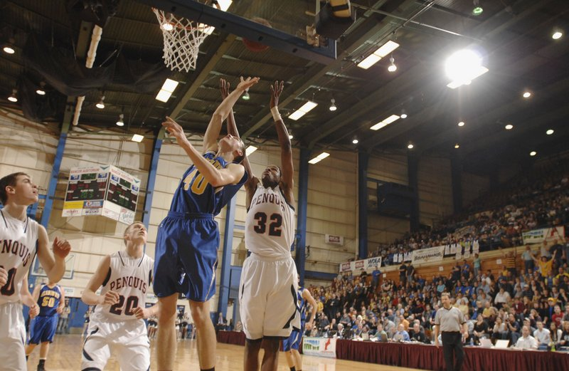 John Hepburn, left, of Boothbay, and Isaiah Bess of Penquis go up for a rebound Saturday night during the last basketball game at the Bangor Auditorium – the Class C boys' state final. Bess scored 27 points to lead Penquis to a 61-54 victory.