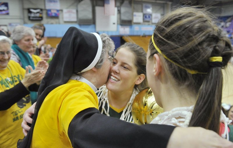 McAuley captains Molly Mack, center, and Allie Clement get a hug from school principal Sister Edward Mary after the Lions won their third consecutive Class A state championship.