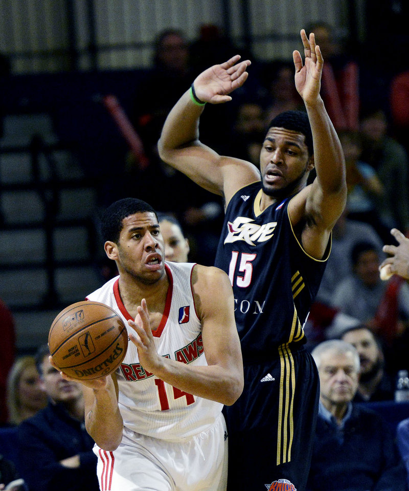 Mark Tyndale of the Red Claws looks for an open teammate while defended by Erie's Mike Singletary.