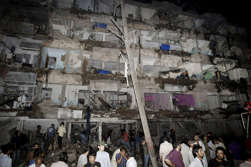 Pakistanis gather at the site of a bombing Sunday in a neighborhood of Karachi dominated by Shiite Muslims.