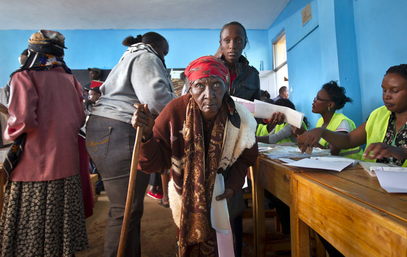 A woman walks with a cane to cast her vote at a primary school near Gatundu, north of Nairobi, in Kenya on Monday.