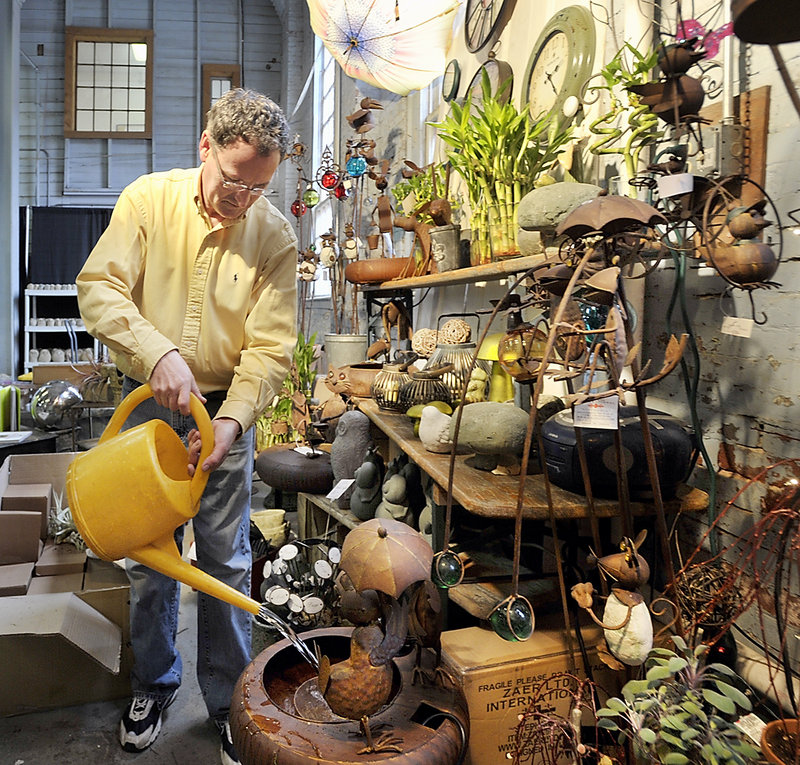 Dan Kennedy, owner of Sawyer Company, fills one of his many whimsical metal sculptured water fountains that move to the flow of the water in his vendor display at the Portland Flower Show on Wednesday, March 06, 2013. He used